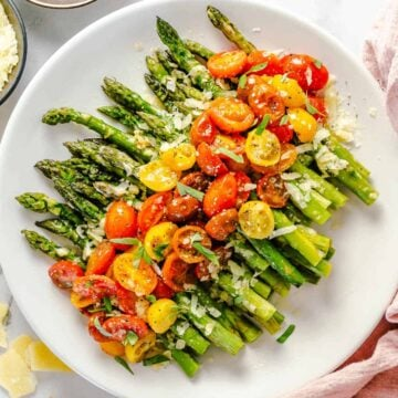flat lay shot of plated asparagus with parmesan and tomatoes on a white plate with pink linen