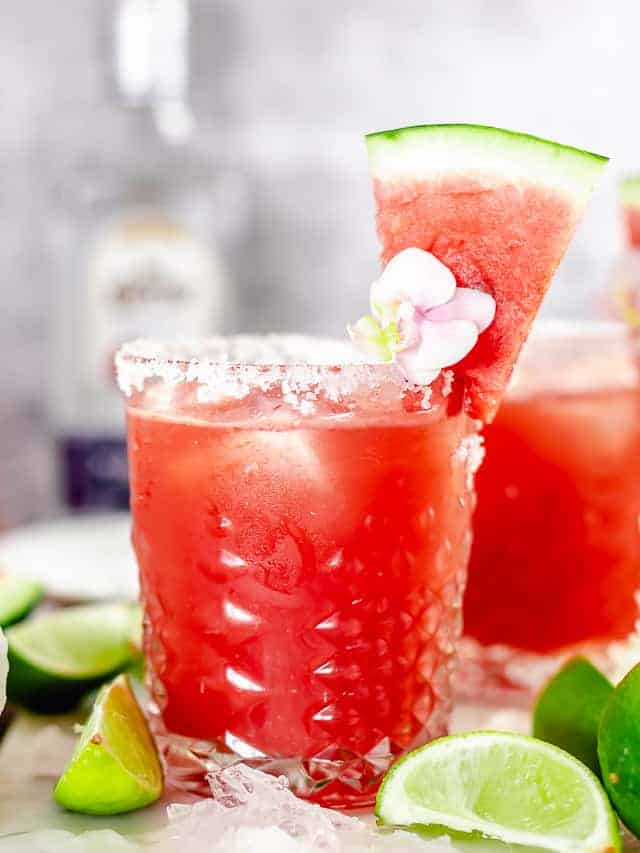 angle view shot of watermelon margarita in whisky glass garnished with purple pink flower, and watermelon slice