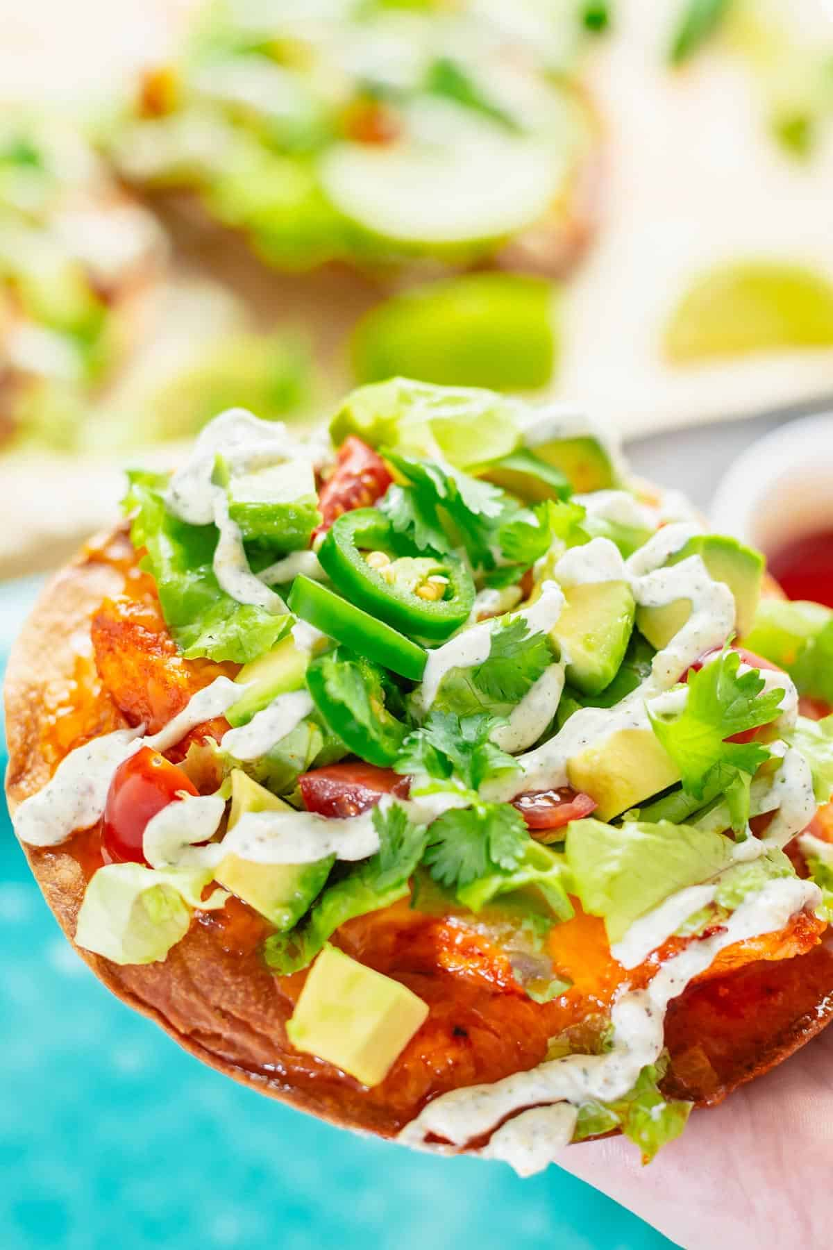 crispy tostadas with buffalo chicken toppings and ranch dressing close up shot