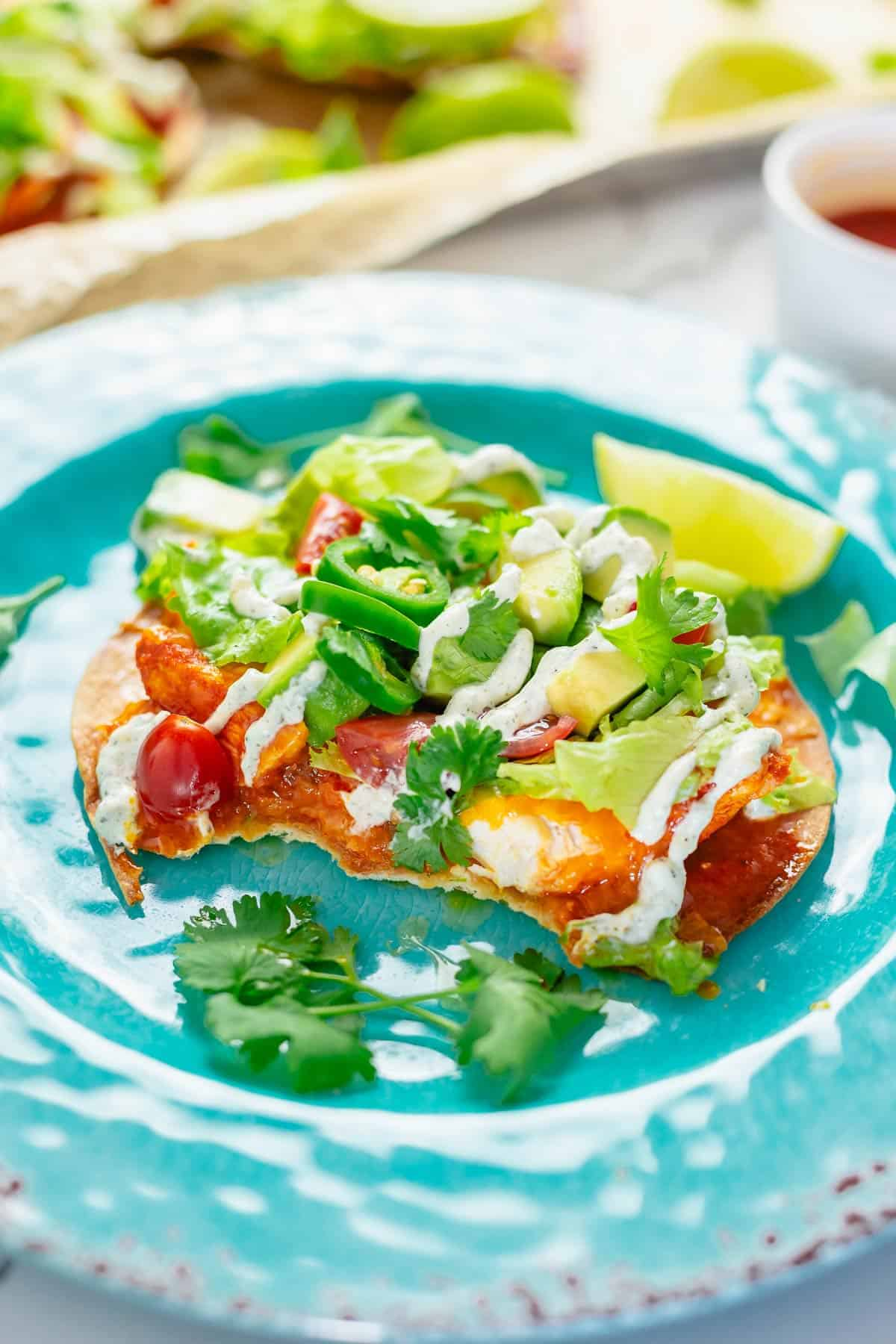 crispy tostadas with buffalo chicken toppings and ranch dressing close up shot on a blue plate