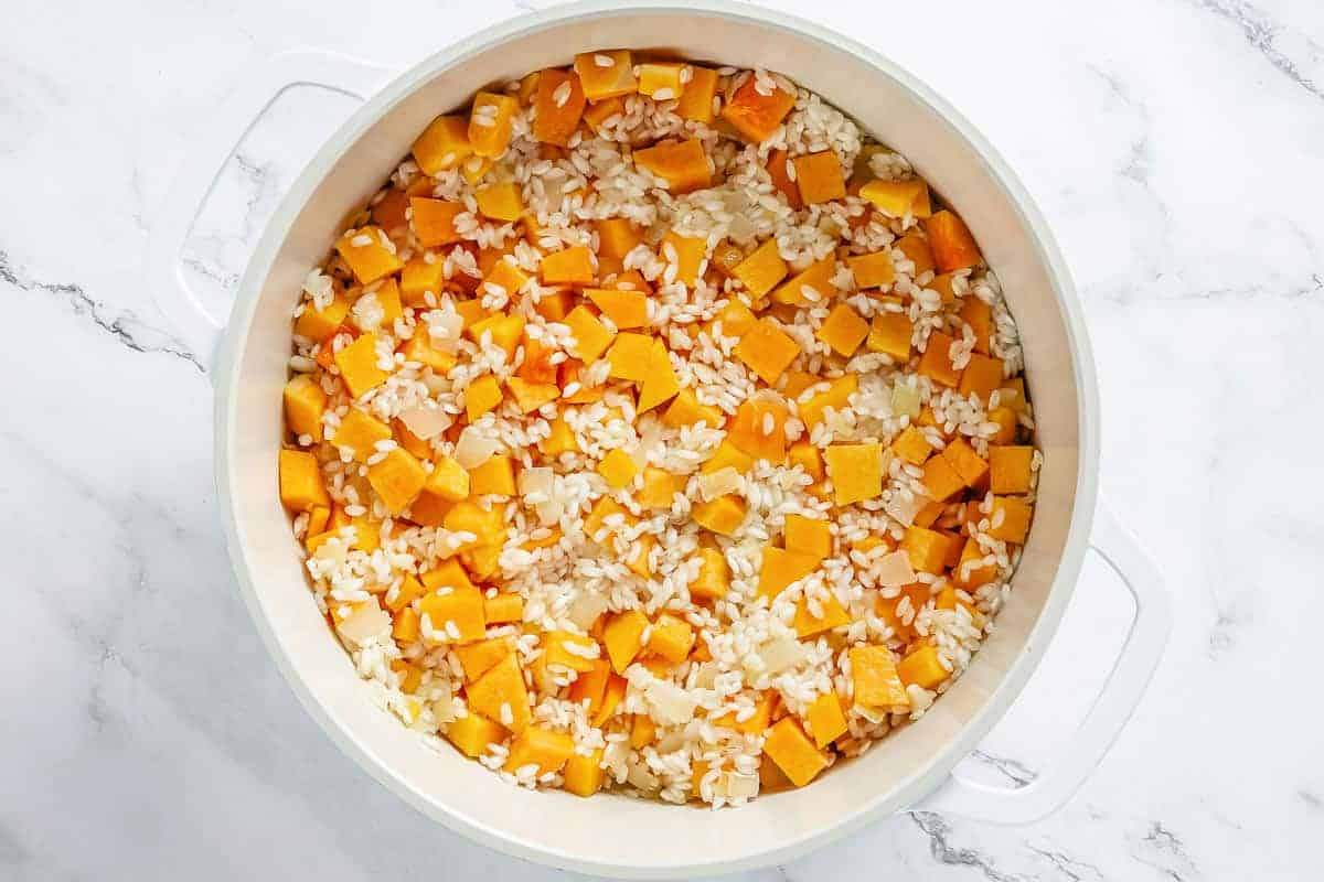 arborio rice and pumpkin pieces sauteeing in a white dutch oven