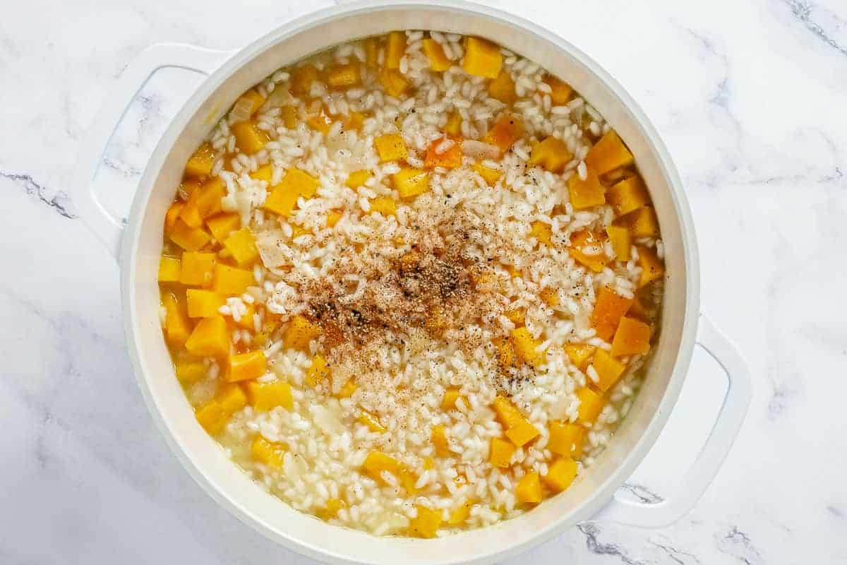 pumpkin risotto ingredients simemring in a white dutch oven