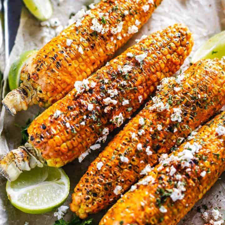 flat lay shot of 4 cajun corn on the cob with feta cheese and parsley
