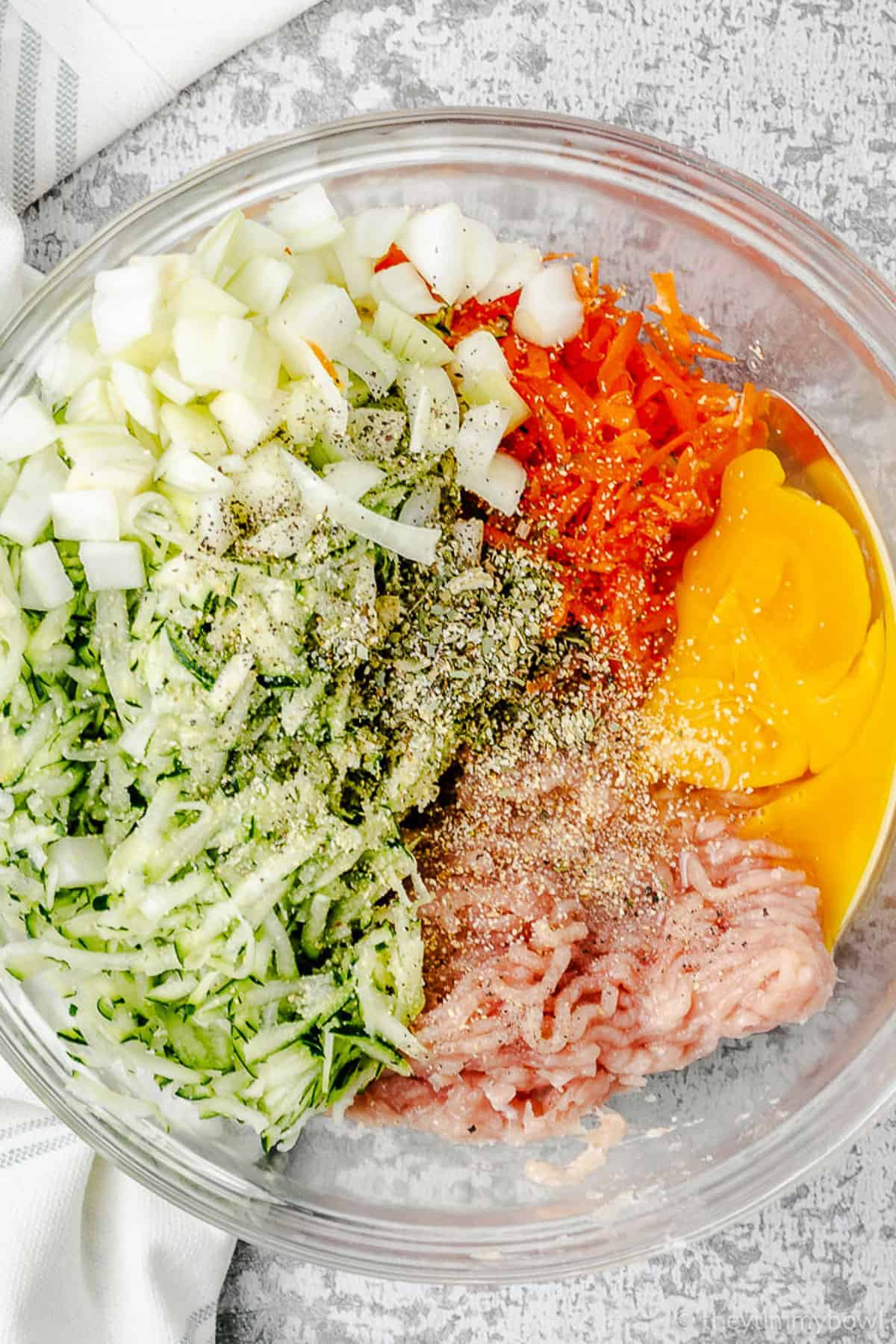grated zucchini ground chicken carrots and egg in a glass bowl