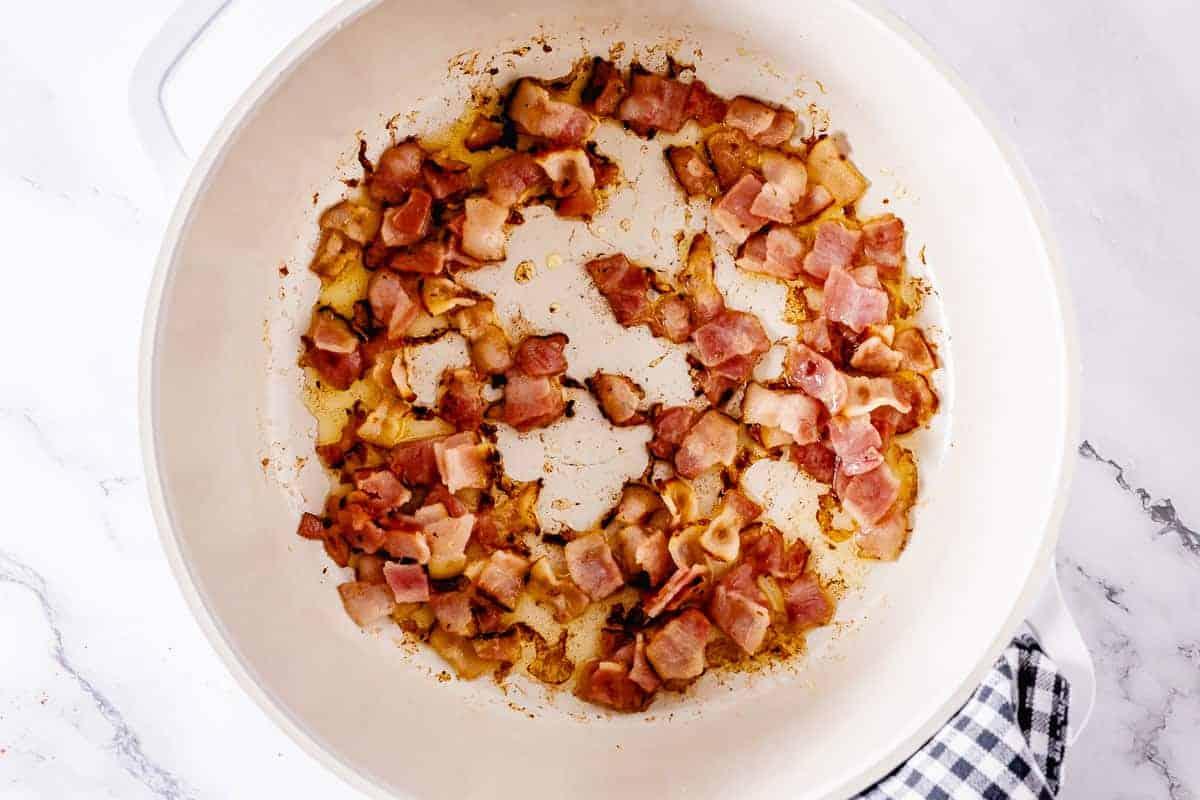Saute bacon in a white pot
