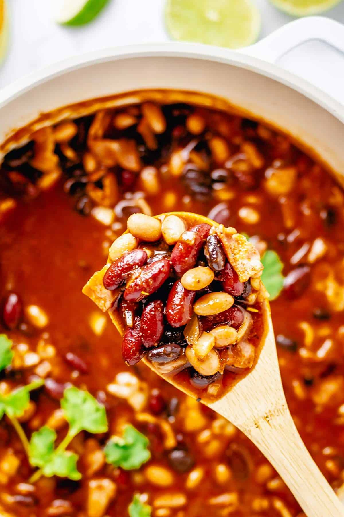 close up shot of cooked beans in tomato sauce on a wooden spoon
