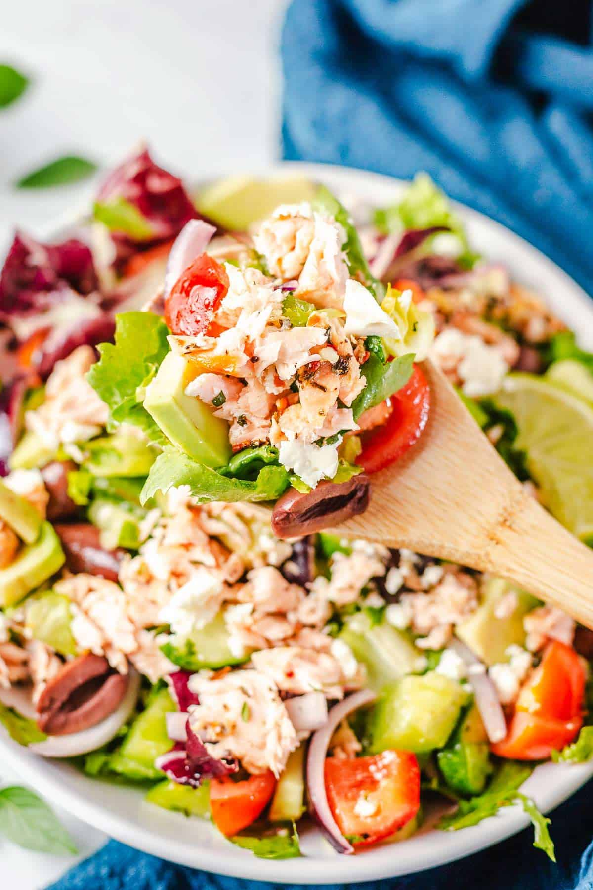 shredded cooked salmon on a wooden spoon with lettuce and vegetables
