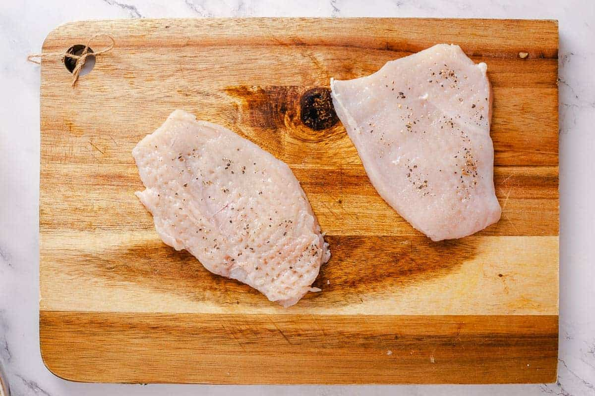 pounded and seasoned chicken breasts on a wooden borad