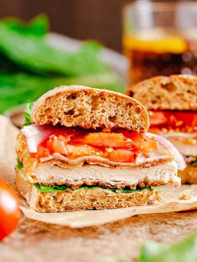 chicken ciabatta sandwich cut out shot over dark background