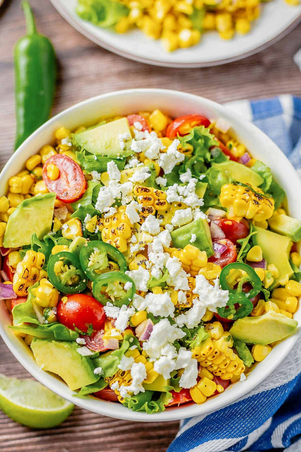 grilled corn salad with lettuce, avocado, tomatoes, onion in a white bowl on a wooden table with blue white striped towel next to it