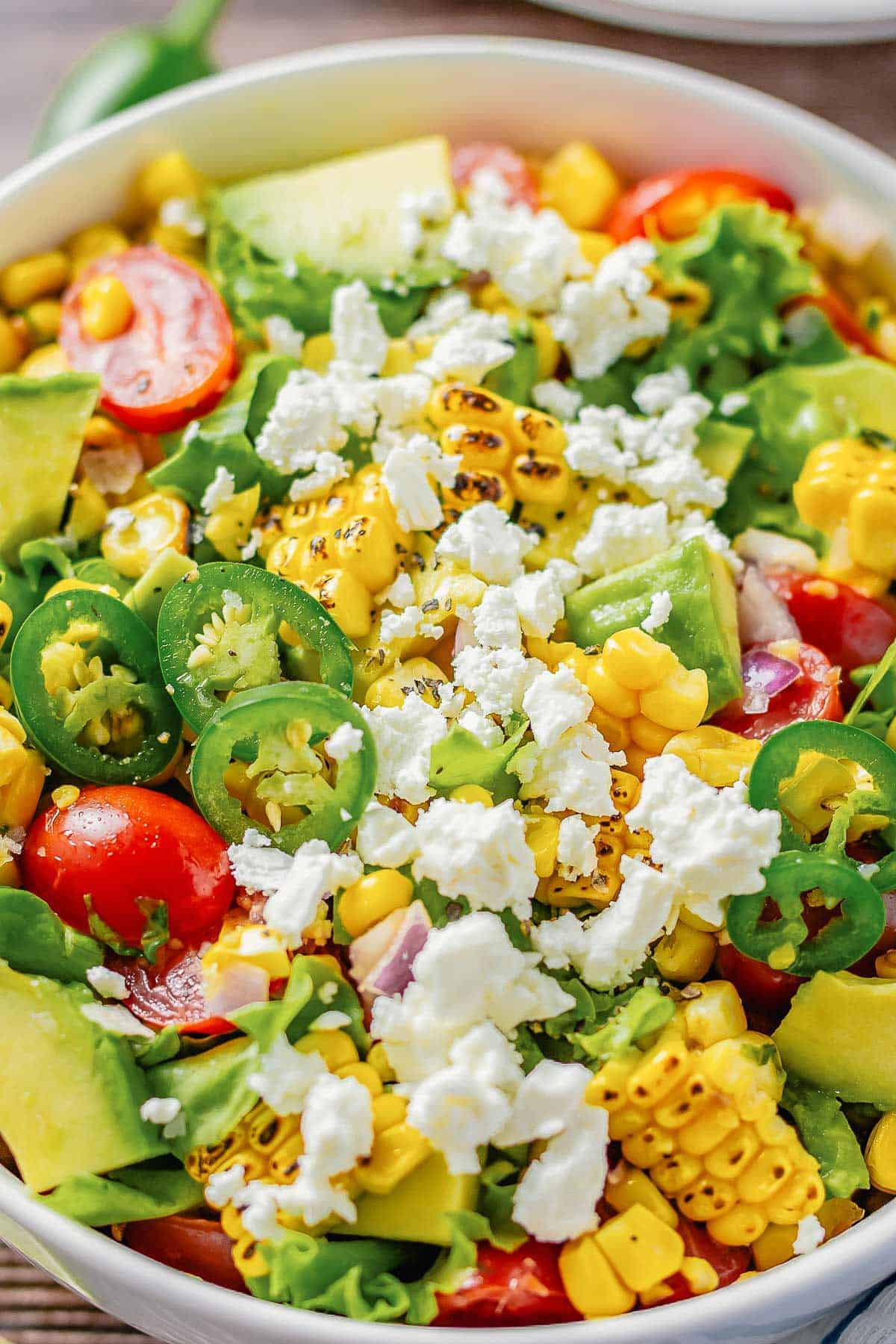 close up shot of a grilled corn salad with lettuce, avocado, tomatoes, onion in a white bowl on a wooden table