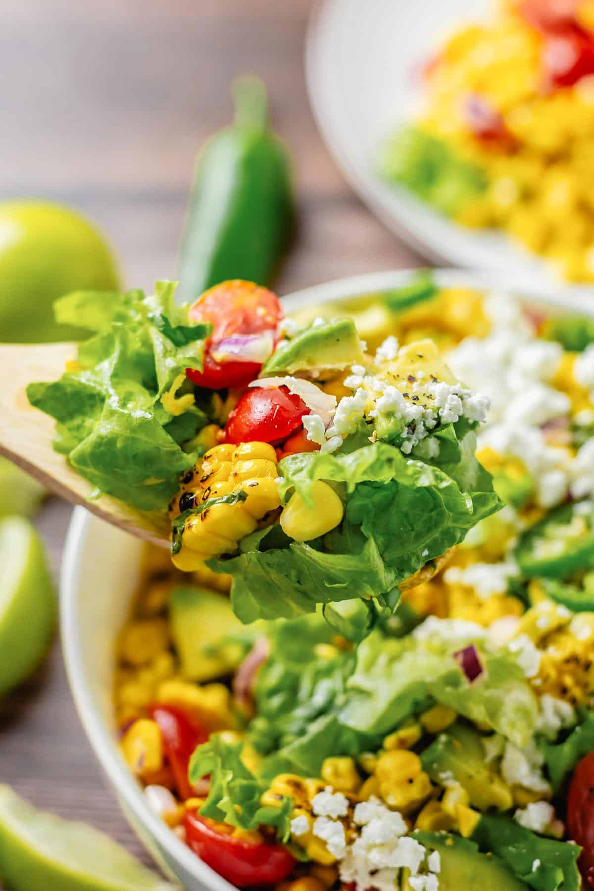 close up shot of wooden spoon with some grilled corn salad with lettuce, avocado, tomatoes, onion in a white bowl on a wooden table