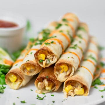 Creamy Chicken Taquitos stacked on top of each other and drizzled with sriracha mayonnaise