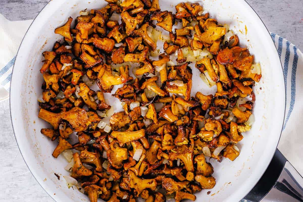 chanterelle mushrooms cooked with butter in a white pan