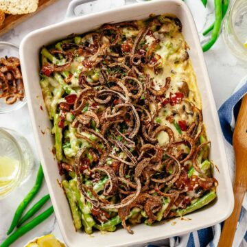 Overhead shot of a baked green bean casserole with bacon on a marble table with lemon slices, scattered green beans, bread and crispy red onions.