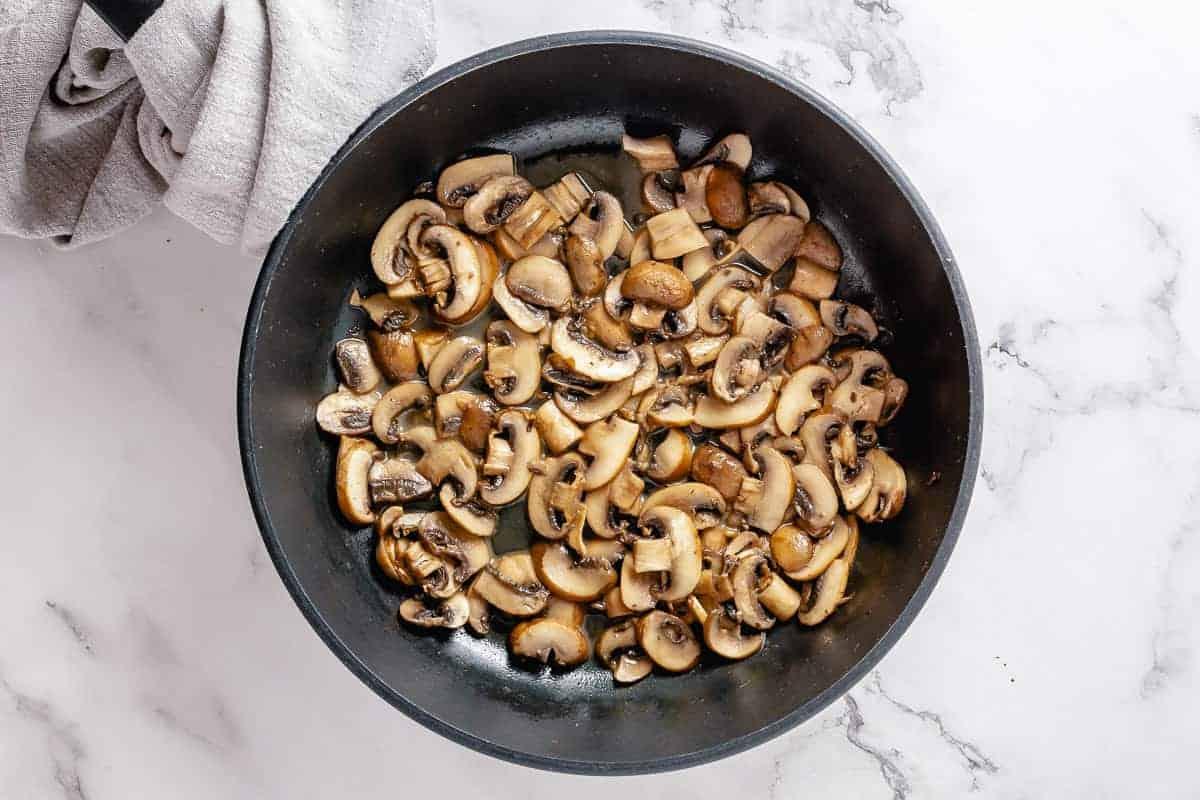 Sliced dark mushrooms frying in a black skillet