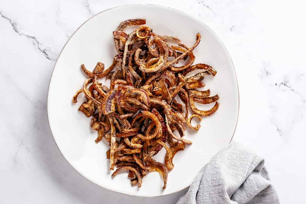 Crispy fried red onions resting on a plate after deep frying