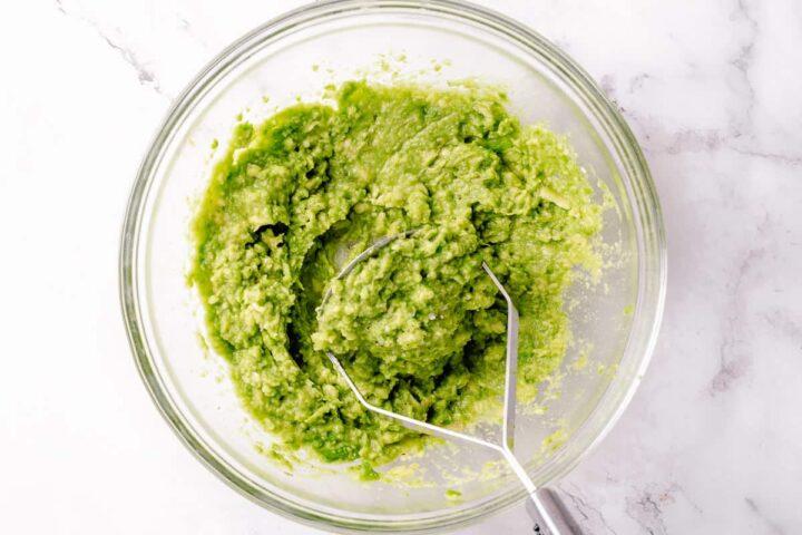 simple guacamole recipe process - mashed avocado in a glass bowl