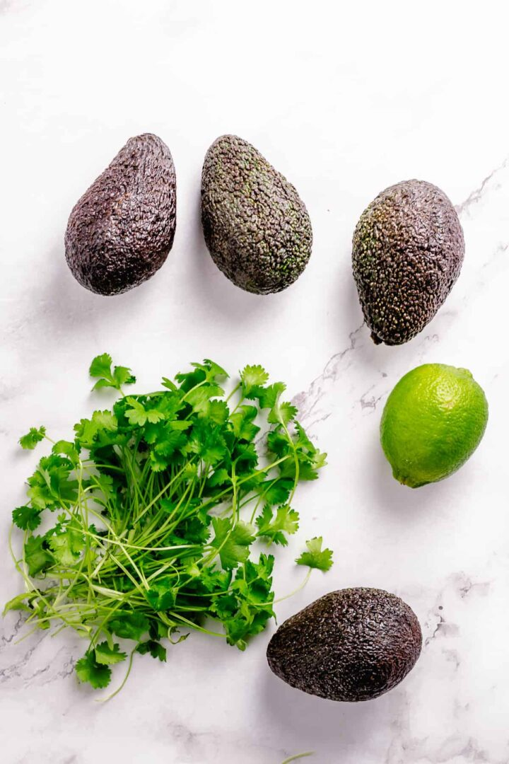 Simple Guacamole recipe ingredients flatlay on a marble background