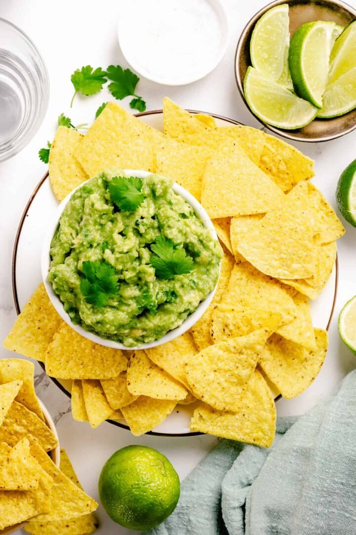 Simple guacamole in a small bowl surrounded with nacho chips flatlay on a marble background