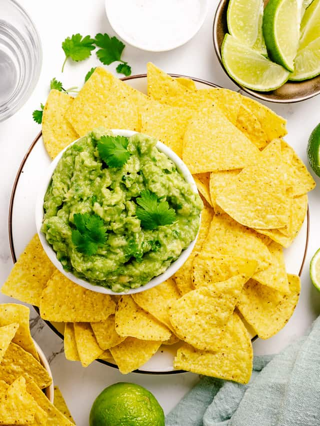 simple guacamole flatlay in a white bowl surrounded with nacho chips on a larger bowl