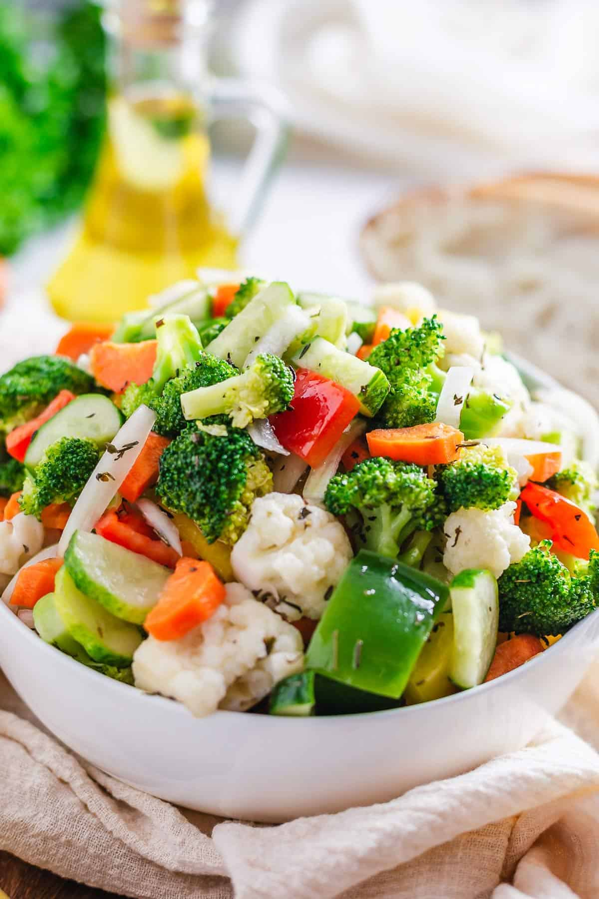 side angle shot of marinated vegetable salad in a white bowl