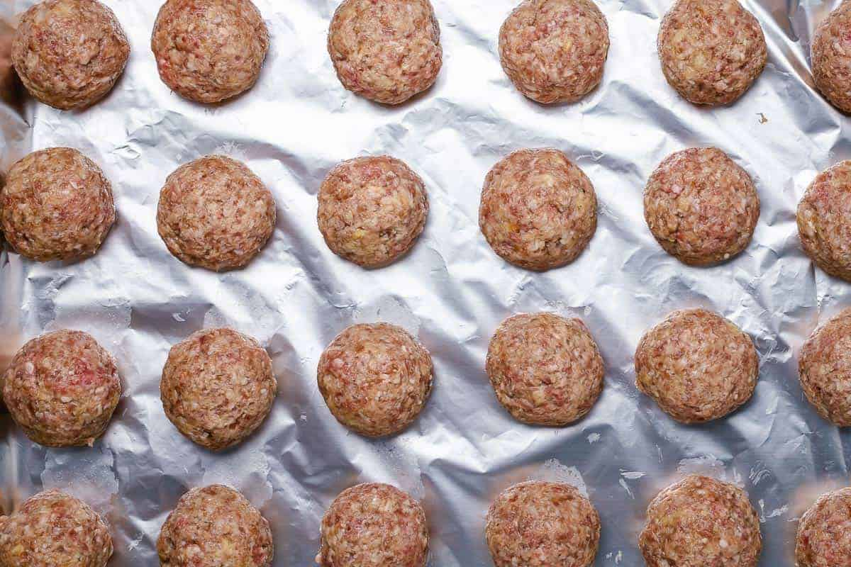 flatlay shot of 24 raw rolled meatballs on a baking sheet lined with foil