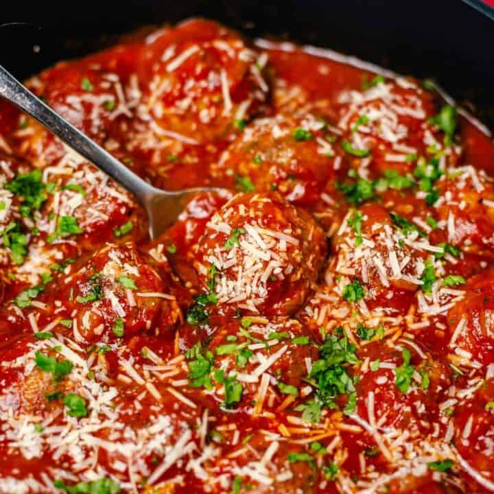 oven baked meatballs simmering in tomato sauce in a black skillet