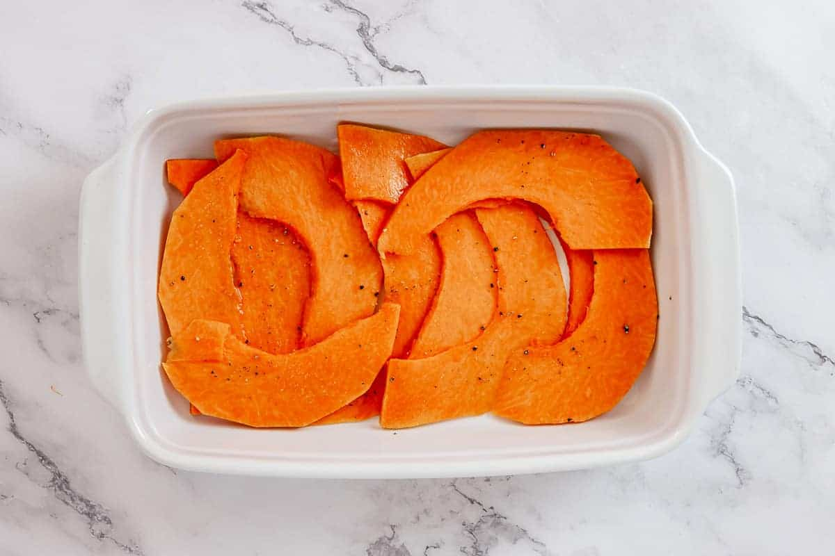 Pumpkin strips in a white casserole dish on a marble table.