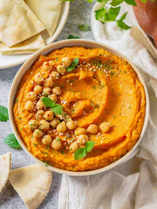 pumpkin and chickpea hummus in a white bowl on a marble table with white linen