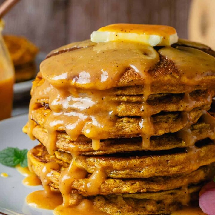 Stacked pumpkin pancakes side view angle with a drizzle of caramel