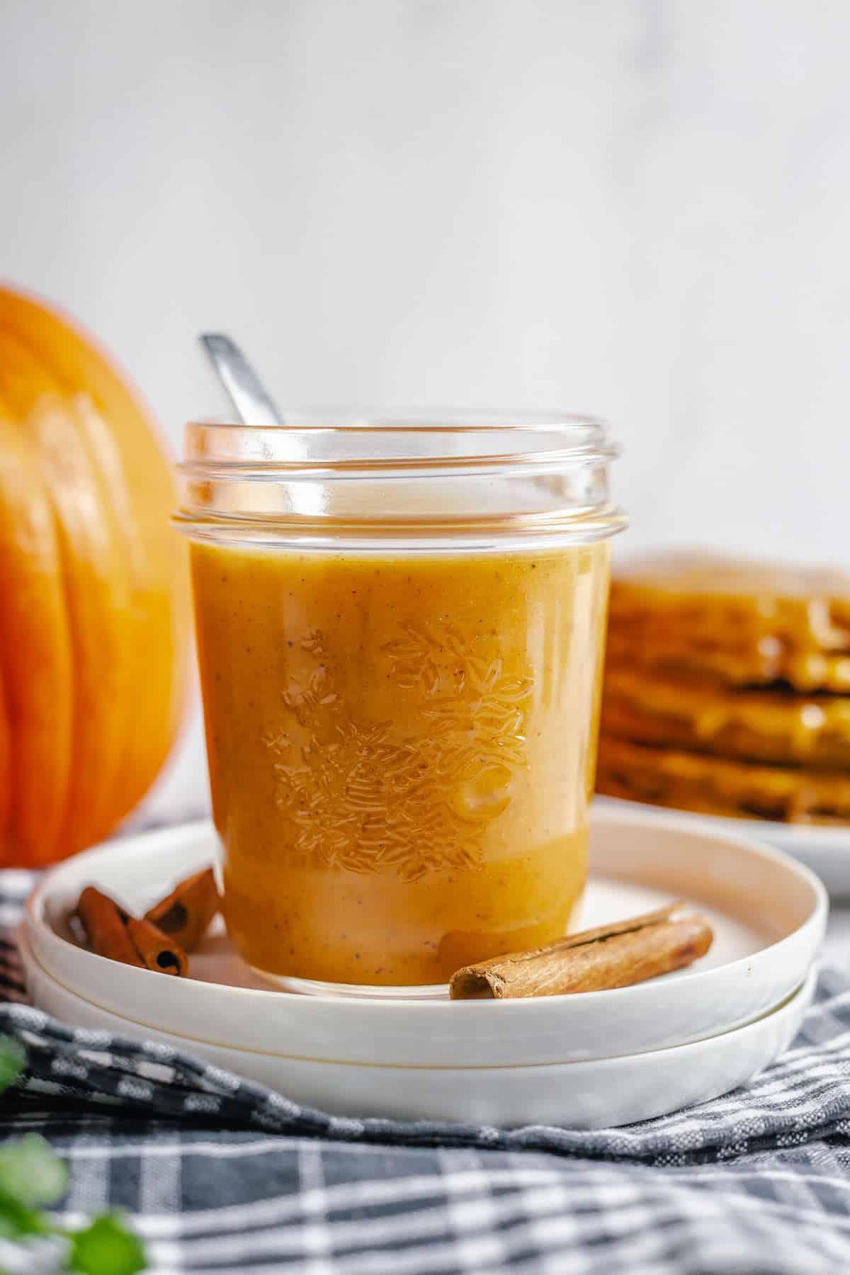 pumpkin caramel sauce in a jar with a pumpkin and pancakes background