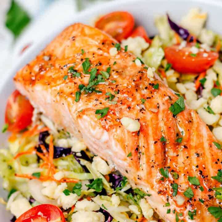 salmon salad bowl in a white bowl with parsley and cabbage