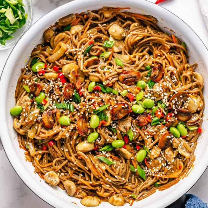Soba Noodles Stir Fry in a white skillet with garnishes