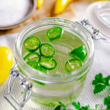 Spicy simple syrup in a small sealed glass container with fresh seeded jalapeno slices inside