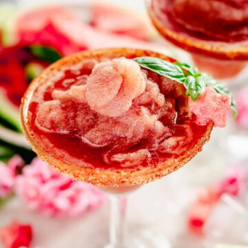 watermelon margarita in a margarita glass served with watermelon star shaped slice and basil leaves