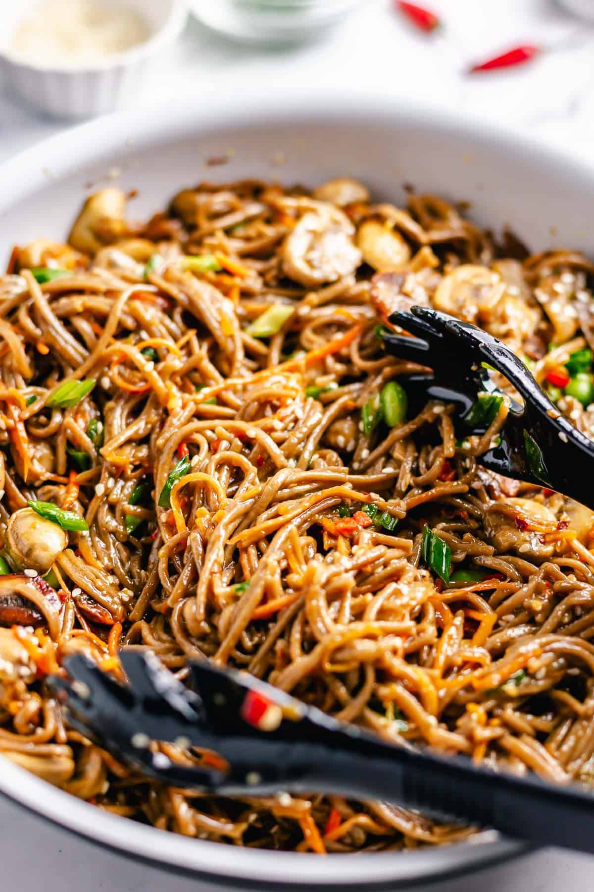 Stir Fry Soba Noodles with black kitchen tongs in a white skillet