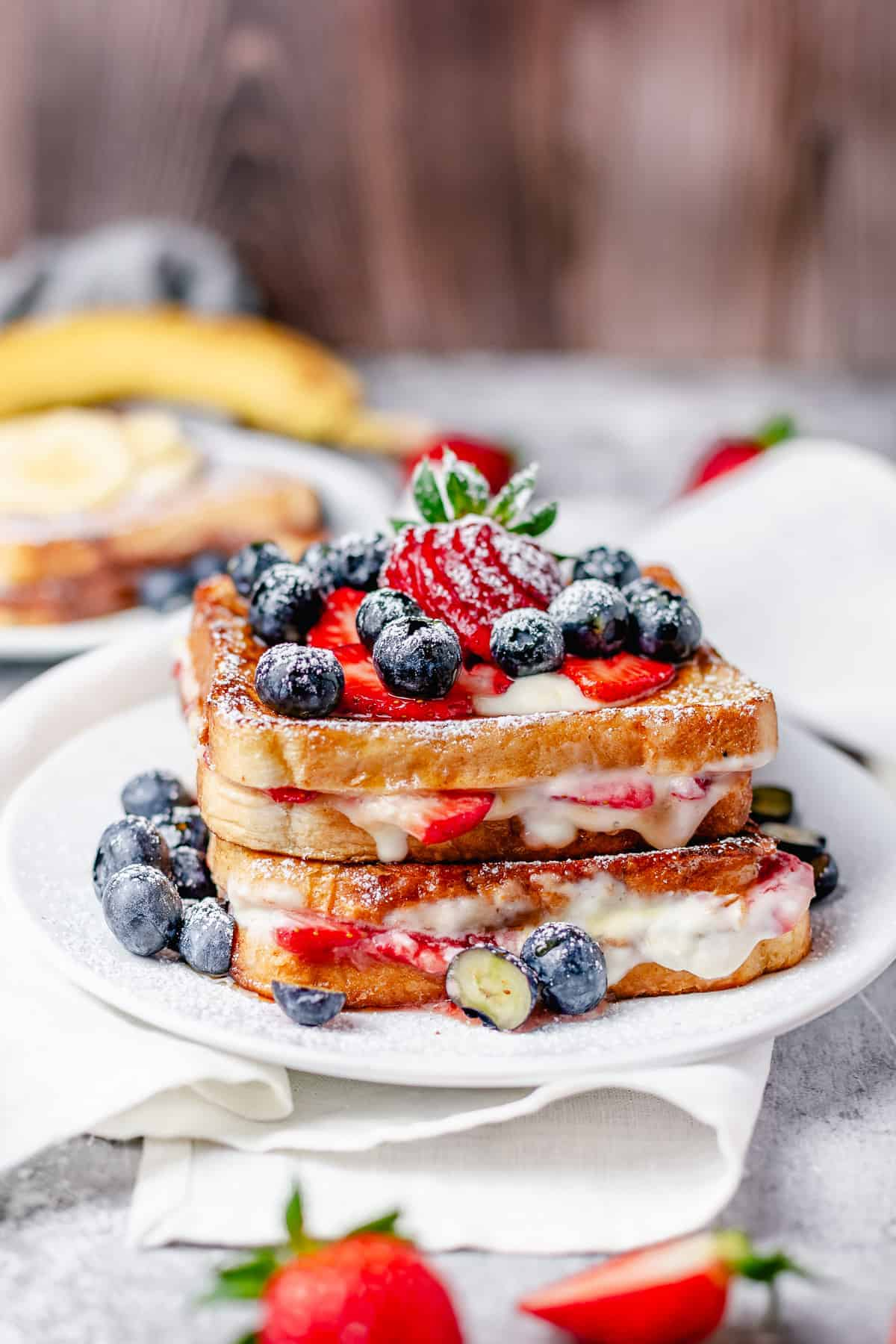 strawberry cream cheese stuffed french toast stacked on a plate