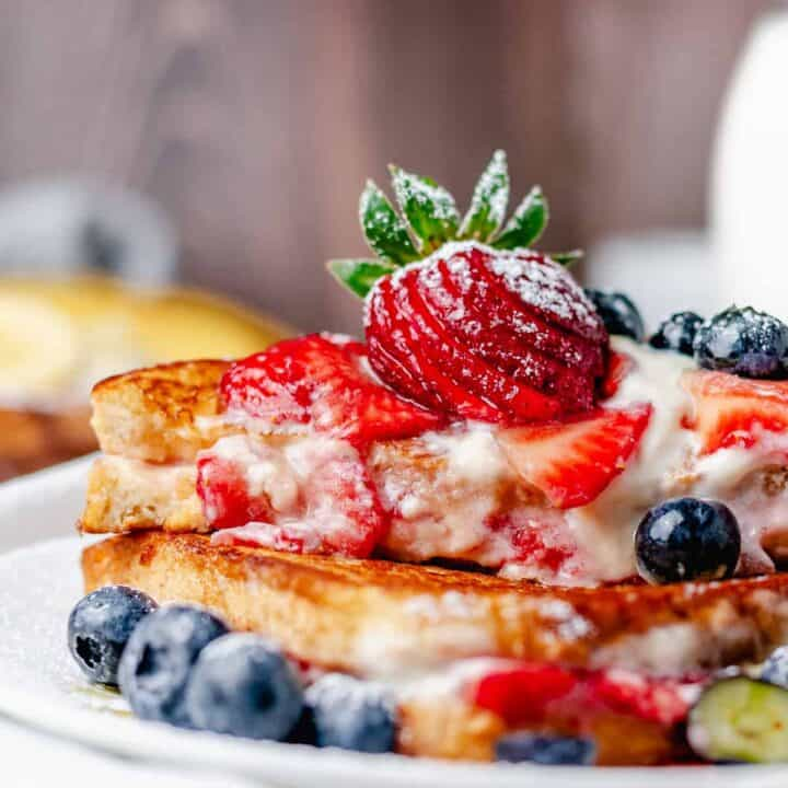 stuffed cream cheese french toast sandwich stack closeup bite shot ona plate with wooden background