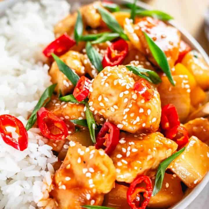 chicken chunks with bell peppers and pineapple in rich sweet and sour sauce in a bowl garnished with chili slices and scallion