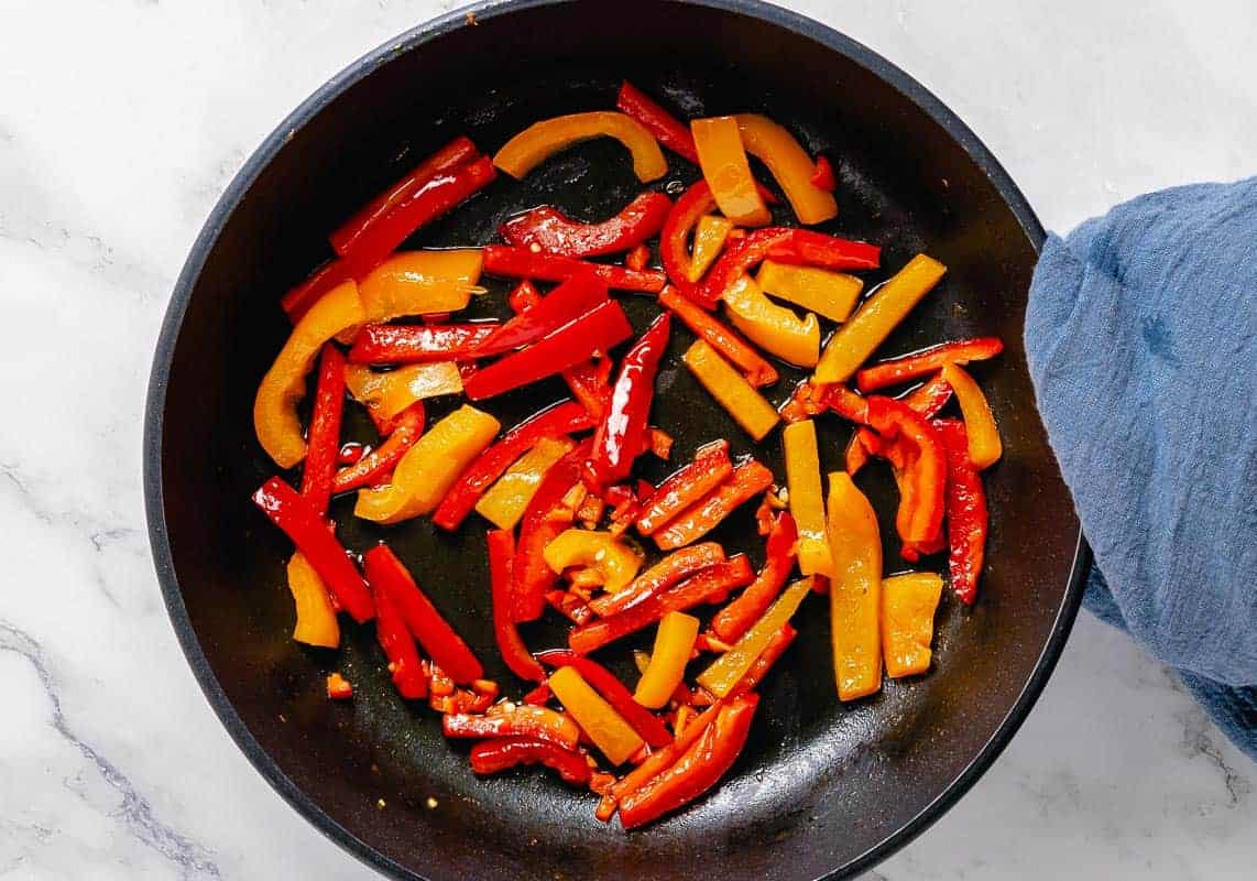 saute bell pepeprs and red hot chili peppers in a black skillet