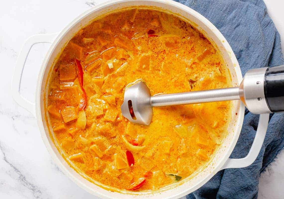 Immersion blender dipped into pumpkin curry pot