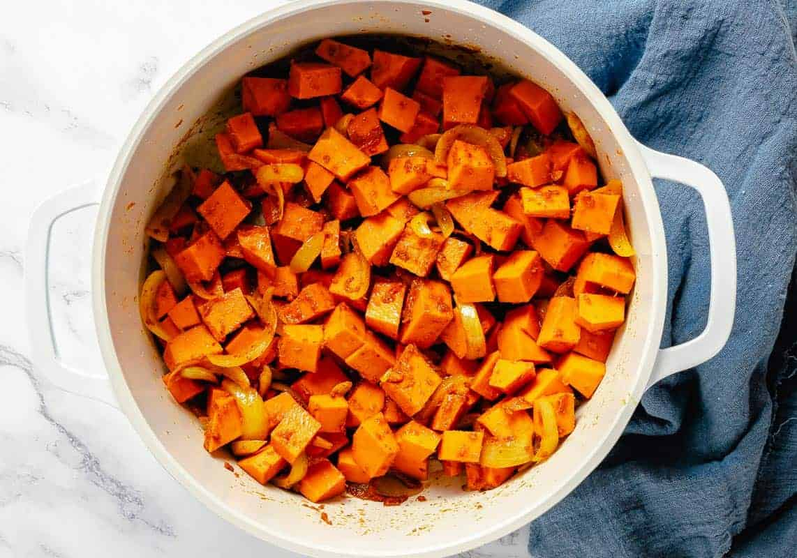 diced pumpkin cubes added to the white pot