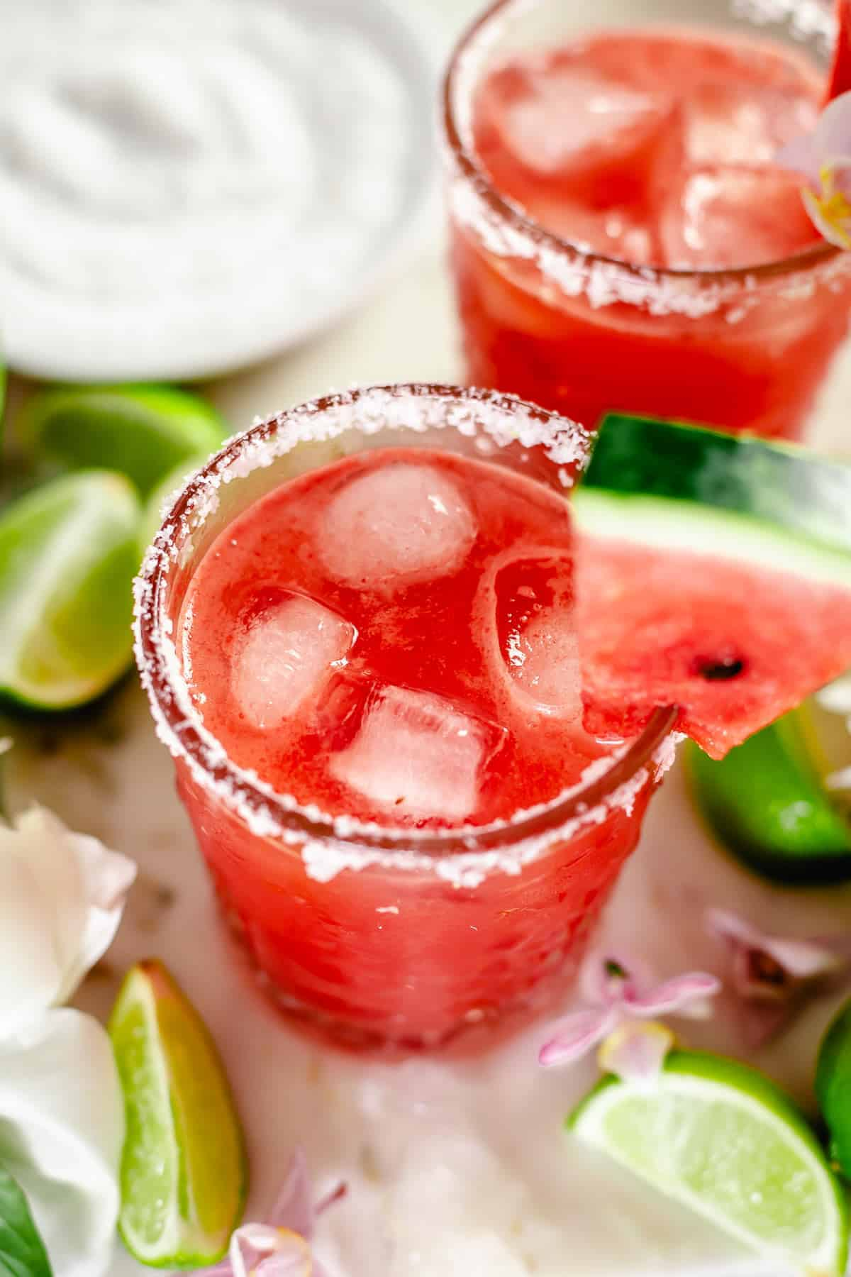 angle view shot of watermelon margarita in whisky glass with salt rim, watermelon slice