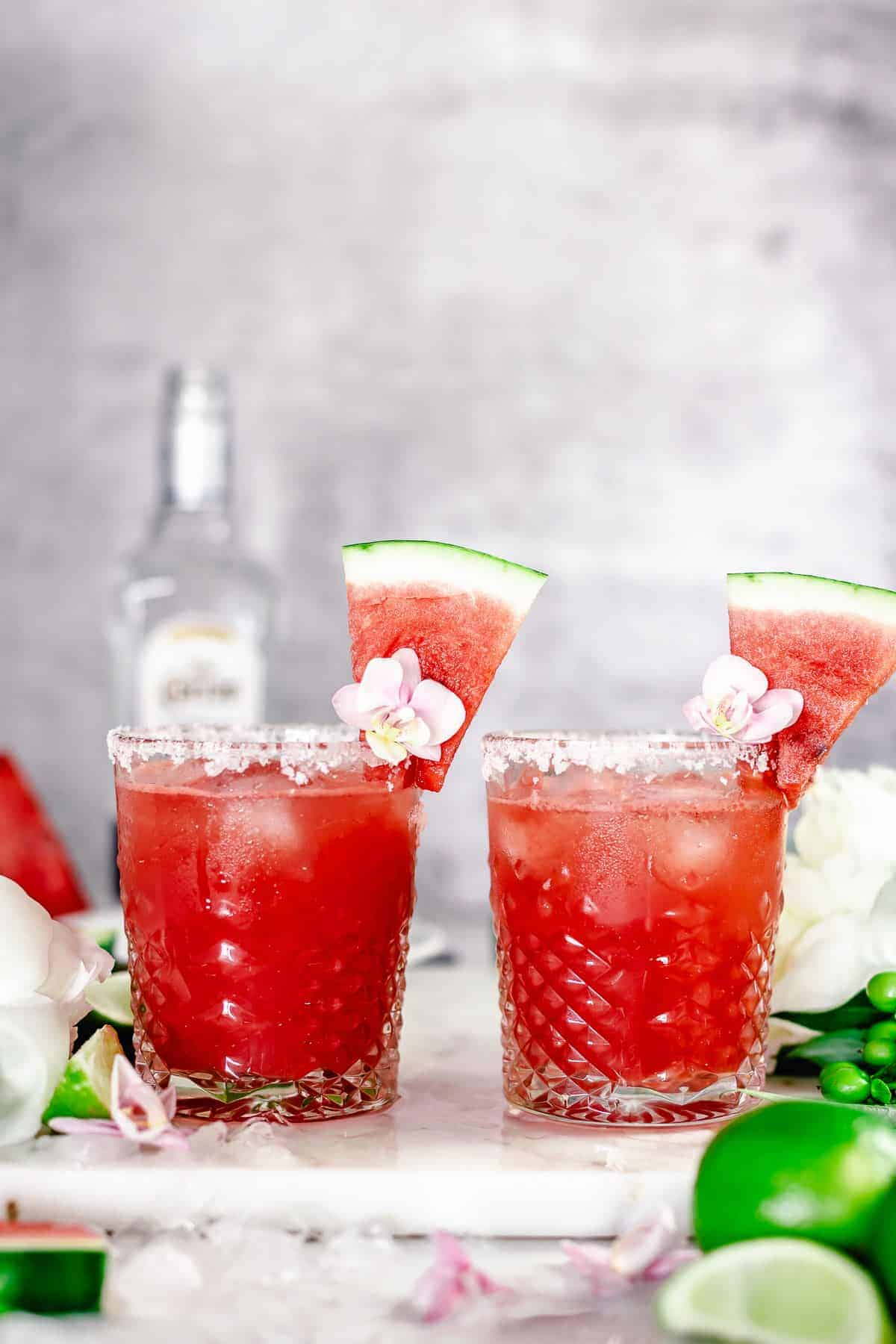 angle view shot of two watermelon margaritas side by side in whiskey glass garnished with purple pink flower, and watermelon slice