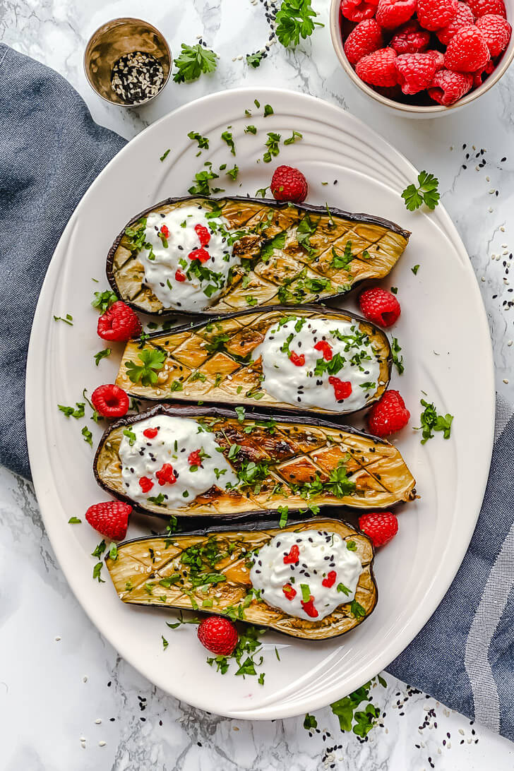 Oven-Roasted Eggplant boats loaded with yogurt and goat cheese dressing and a bit of raspberry together create a delicious and delicate flavor that almost asking to be eaten immediately.