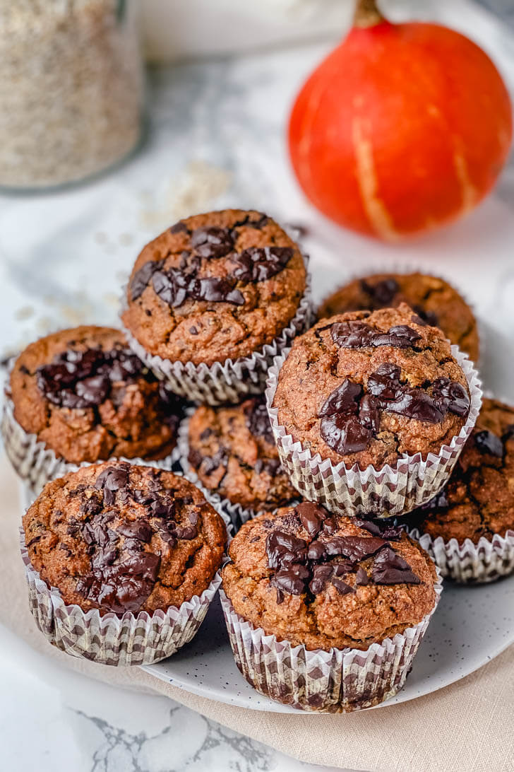 An easy recipe for pumpkin muffins. These oat flour pumpkin muffins are gluten-free, filled with chocolate, nuts and have no refined sugar. They're deliciously soft and moist, perfect to enjoy with a warm cup of coffee at breakfast. #glutenfreepumpkinmuffins #glutenfreepumpkinmuffinseasy #glutenfreepumpkinmuffinsalmondflour #glutenfreepumpkinmuffinsoatmeal #pumpkinchocolatechipmuffins