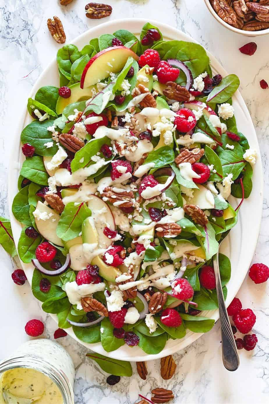 Raspberry, Spinach, and Beet Green Salad - healthy, summer salad recipe loaded with raspberries, pecans, fresh spinach, feta, and beet leaves. This recipe uses just a few ingredients and is simply delicious on its own. But what makes this salad unforgettably delicious is the Creamy Greek Yogurt Herb Dressing. - The Yummy Bowl