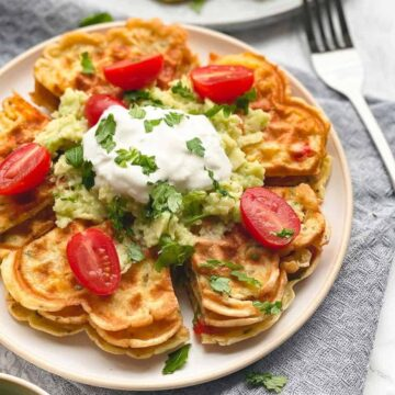 These Savory waffles with cheddar, spring onion, and feta are cheesy, warm, a bit crispy, and are loaded with your favorite vegetables. Perfect recipe idea for a Sunday breakfast with your family. By the way, these waffles are gluten-free and vegetarian! Crispy outside and chewy on the inside. - The Yummy Bowl