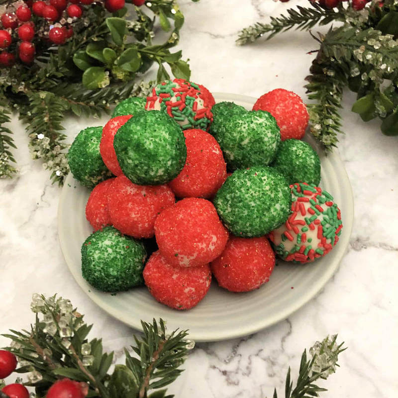 Red and green moscato truffle balls on a white plate with christmas decorations around them